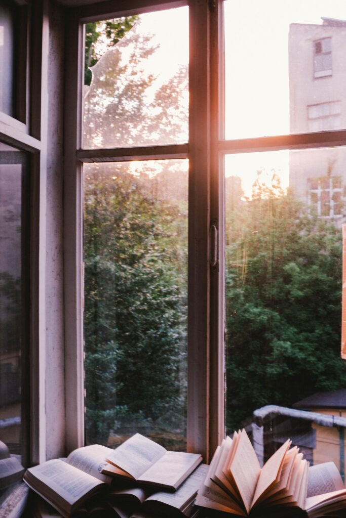 sunlight coming through the top of a window. Greenery and a building can be seen out the window. inside of the window, at the bottom of the picture is books open.