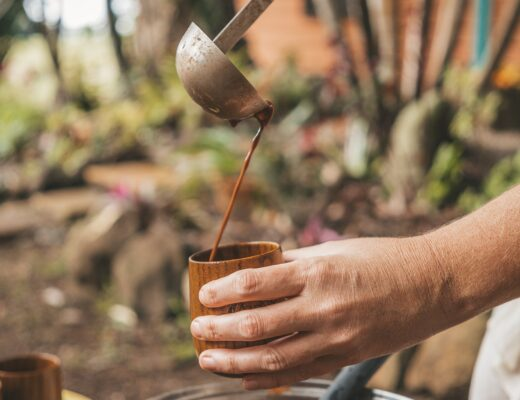 person pouring cacao into a wooden cup