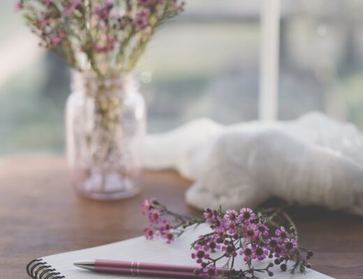 A blank journal with a pen and springtime flowers lying on the journal. A vase of flowers is in the background.